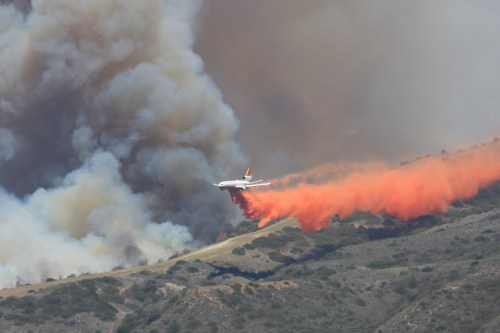 A plane drops fire retardant onto a 25-acre fire burning in Camp Pendleton. Photo: Andrea Swyane
