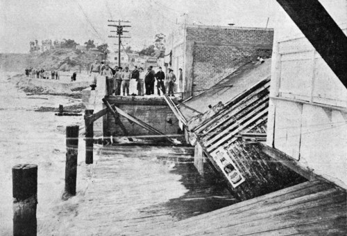 Onlookers observe damage to Carl Benson's hotdog stand along the Laguna Beach boardwalk after flood waters rushed the shore in March 1938. Courtesy of Orange County Archives