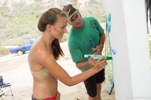 Drew Brophy, a San Clemente artist and surfer (shown here at San Onofre welcoming the participation of a beachgoer) hopes to inspire and be inspired by the community through a weeklong surf art project at local surf breaks and surf shops. Photo: JoniePHOTO