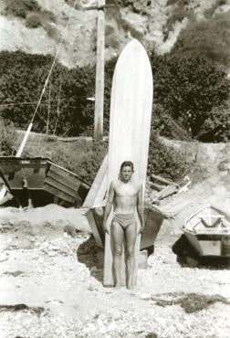 """Mel Pierce will be named Dana Point Historical Society Patriarch at the organization's May 13 meeting. Pierce is shown here with his Lorrin """"Whitey"""" Harrison-made redwood and balsa board at the foot of Cove Road, circa 1938. Photo: Courtesy of the Dana Point Historical Society"""