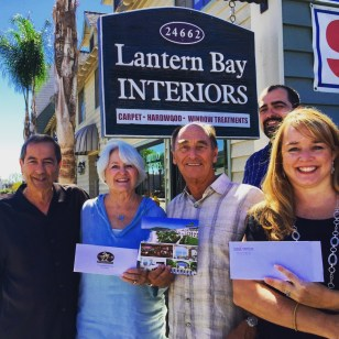 Lantern Bay Interiors & Flooring owner Gene DeCollibus, Linda Theel, Bob Theel, Mike DeCollibus (Lantern Bay Interiors) and Heather Johnston, Chamber of Commerce executive directors gather to present the Theels with their Shop Del Prado prizes for the June drawing. The Theels won with a receipt from a carpet purchase at Lantern Bay Interiors. Photo: Courtesy of the Dana Point Chamber of Commerce