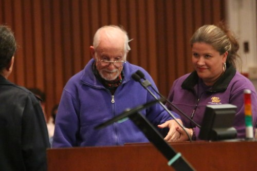 An 82-year-old man, who said he emigrated to the United States years ago, is helped to the podium to speak about his need for a hospital and emergency room in San Clemente. Photo: Eric Heinz