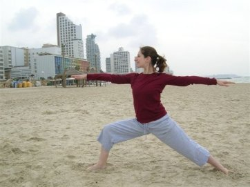 Deborah Friedes stretching on a beach in Tel Aviv