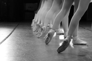 A black and white photo of the legs of dancers, they are at a ballet lesson.