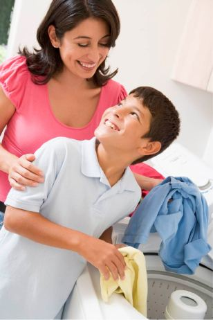 Mother helping her son learn to do laundry