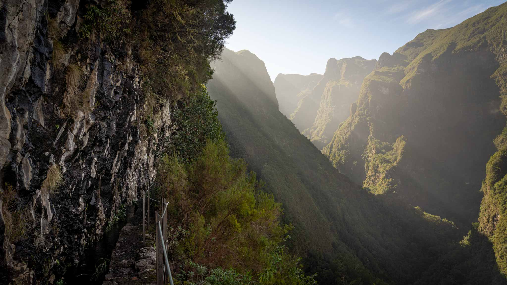 Rays of sun beam across the mountains and the Levada do Caldeirão Verde walking path is on the left