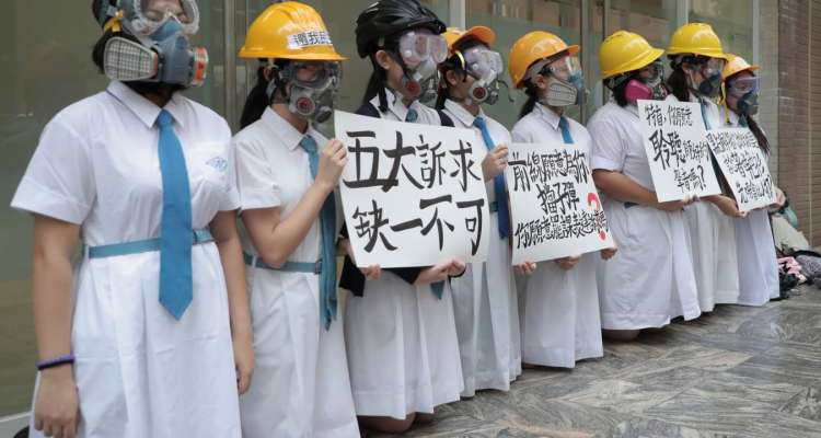 "Students wearing gas masks and helmets hold a banner which reads ""Five major demands are indispensable."",  at St. Francis' Canossian College in Hong Kong, on Monday, Sept. 2, 2019. Hong Kong has been the scene of tense anti-government protests for nearly three months. The demonstrations began in response to a proposed extradition law and have expanded to include other grievances and demands for democracy in the semiautonomous Chinese territory. (AP Photo)"