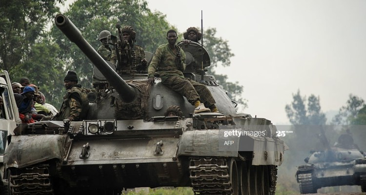 Congolese army tanks retreat through the village of Rugari, some 37 kms from Goma, following an alleged ambush by M23 rebels in the Democratic Republic of the Congo's restive North Kivu province on July 26, 2012. This area has seen heavy fighting over the past three days, displacing thousands of people and increasing fears of a move by M23 on the provincial capital. Heavy fighting has continued today around Rumangabo, the headquarters of the Virunga National Park, just several kilometres from Rugari. AFP PHOTO/PHIL MOORE        (Photo credit should read PHIL MOORE/AFP/GettyImages)