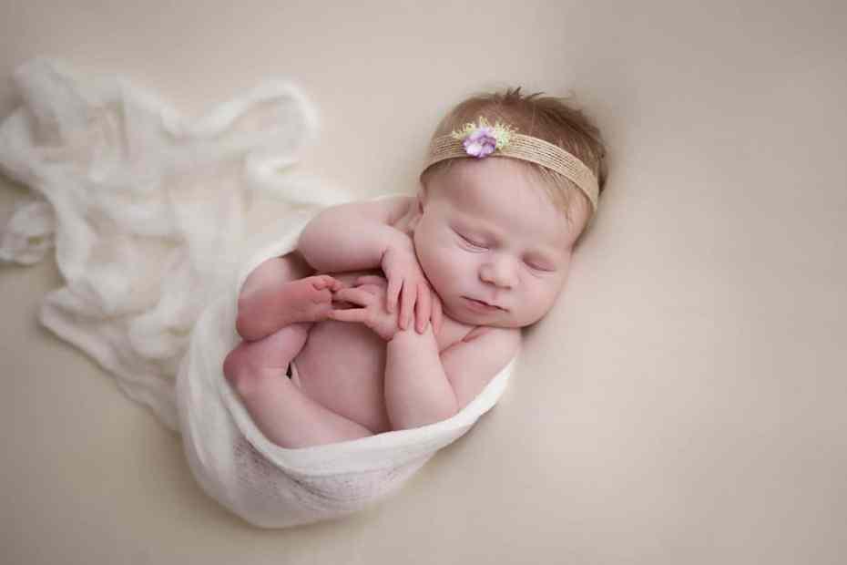 newborn curled up in wrap