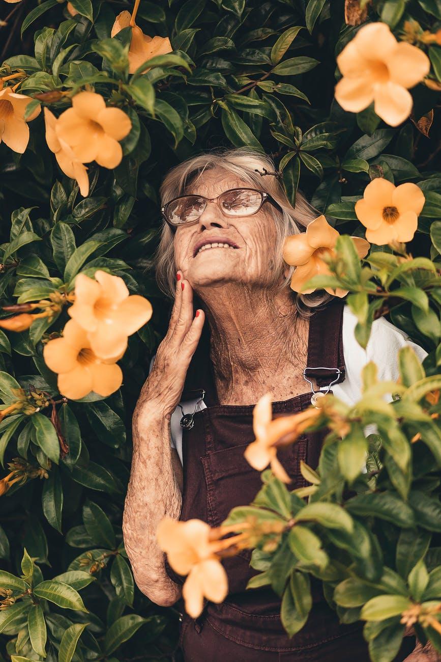 woman smiling standing on yellow bell flower plant, een dagje ouder