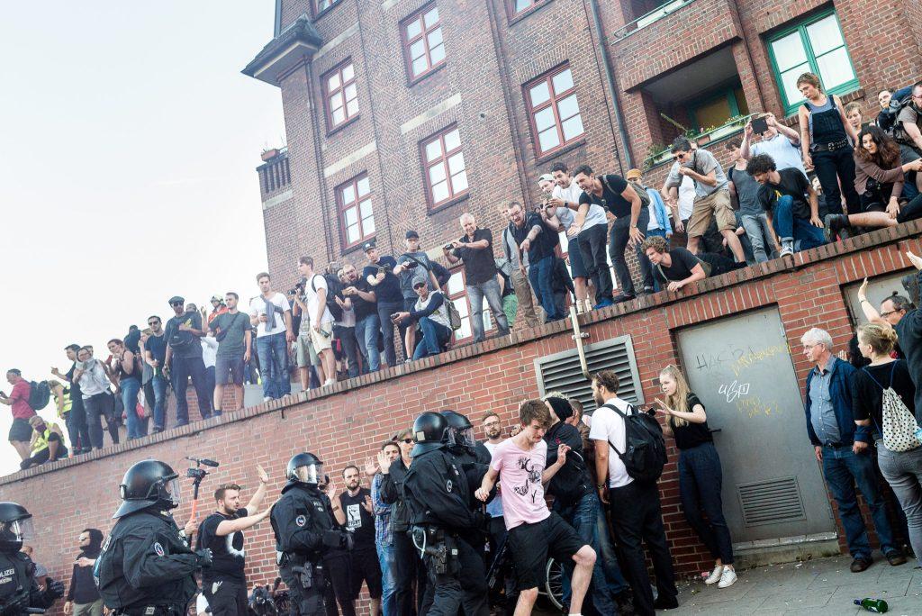 """Demonstranten versuchen sich auf die Mauer beim Fischmarkt zu retten, nachdem die """"Welcome to hell"""" Demo eskalierte und die Polizei völlig frei dreht."""