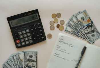 black calculator beside coins and notebook