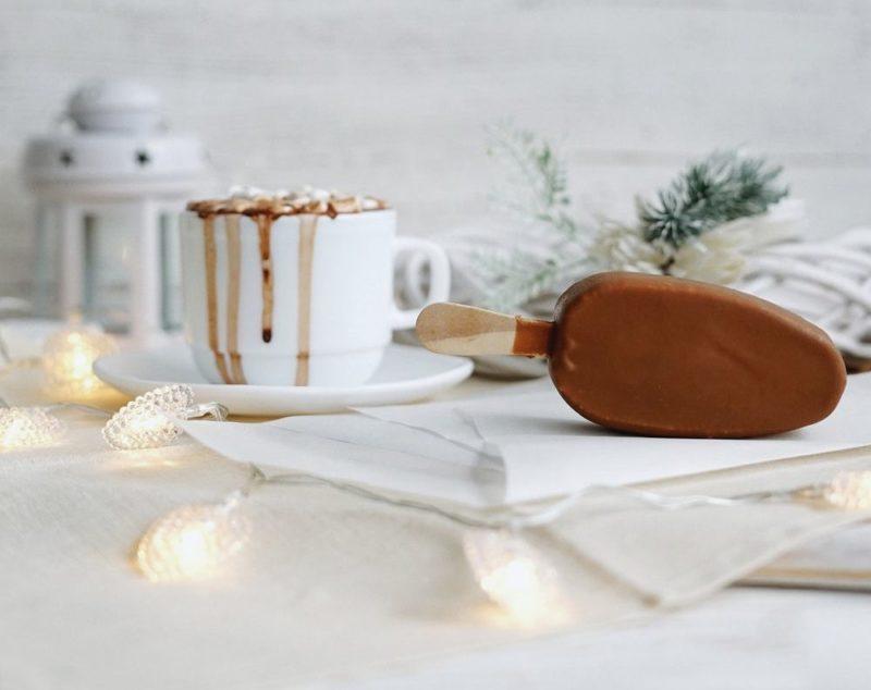 zdjęcie stołu z filiżanką czekolady, lodem na patyku, latarenką oraz ozdobą świąteczną, światełkami i gałązką choinki