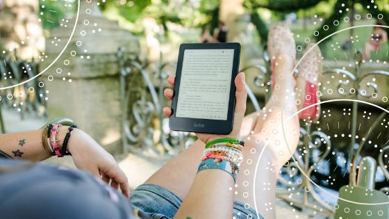 Kobieta siedząca na balkonie  czyta ebooka na czytniku.