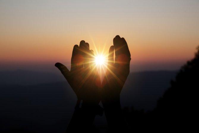 Zwei Hände vor der Sonne im Sonnenuntergang