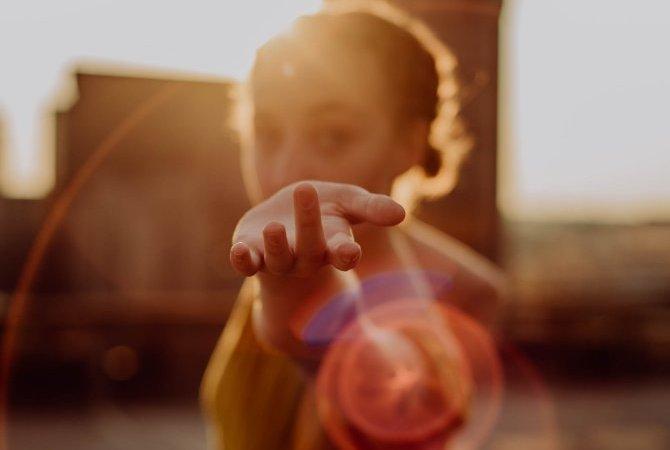 Junge Frau streckt den Arm nach uns aus, im Sonnenuntergang
