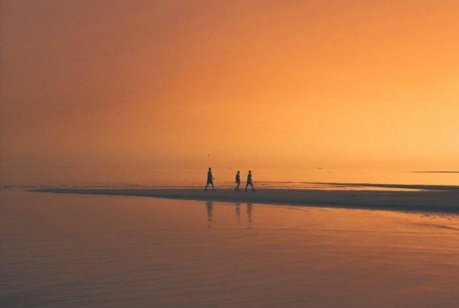 Drei Personen am einsamen Strand im Orangeton