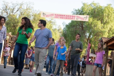 Group walking with Boysenberry Festival Banner Behind
