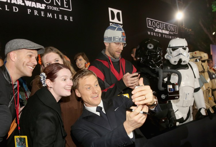 "HOLLYWOOD, CA - DECEMBER 10: Actor Alan Tudyk (C) takes a selfie with fans at The World Premiere of Lucasfilm's highly anticipated, first-ever, standalone Star Wars adventure, ""Rogue One: A Star Wars Story"" at the Pantages Theatre on December 10, 2016 in Hollywood, California. (Photo by Jesse Grant/Getty Images for Disney) *** Local Caption *** Alan Tudyk"
