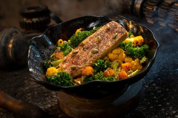 Innovative and creative eats from around the galaxy will be available at Star Wars: GalaxyÕs Edge when it opens May 31, 2019, at Disneyland Park in Anaheim, Calif., and Aug. 29, 2019, at Disney's Hollywood Studios in Lake Buena Vista, Fla. The Oven-roasted Burra Fish, found at Docking Bay 7 Food and Cargo inside Star Wars: GalaxyÕs Edge, features Dijon-crusted sustainable fish with mixed greens, roasted vegetables, quinoa and pumpkin seeds with a creamy green curry ranch dressing. (David Roark/Disney Parks)