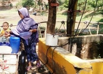 Seorang ibu bersama anaknya yang masih kecil memanfaatkan air sumur di tepian Situ Sipatahunan, Kecamatan Baleendah, Kabupaten Bandung, Jawa Barat. Air yang kurang bening itu untuk memenuhi kebutuhan sehari-hari karena air di rumahnya mulai surut dampak dari musim kemarau. Foto:dara.co.id/MuhammadZein