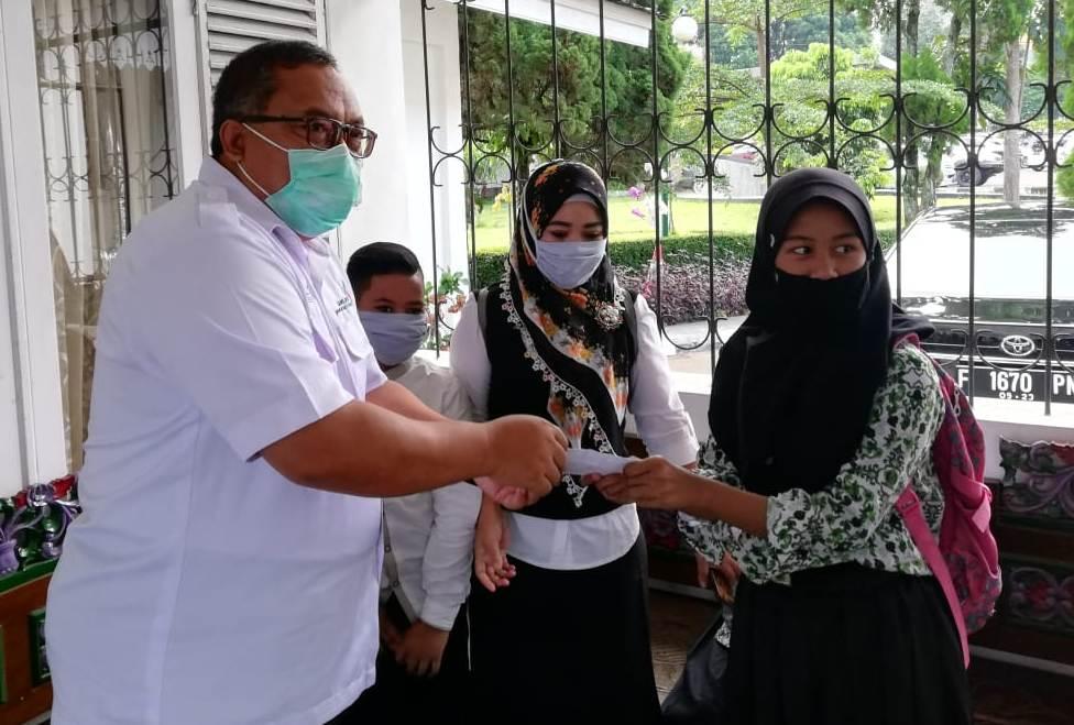 Bupati Sukabumi, Marwan Hamami secara simbolis menerima bantuan dari perwakilan pelajar di Kabupaten Sukabumi, Jawa Barat, untuk penanganan pandemi Covid-19 di Rumah Jabatannya, Kamis (23/4/2020). (Foto: Riri Satiri/dara.co.id)