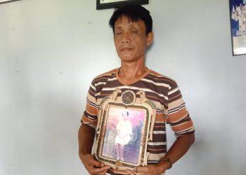 Paman Korban, Ahmad Saputra (51) saat memegang foto korban (Foto: Purwanda/dara.co.id)