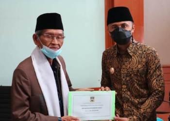 Plt Bupati Bandung Barat Hengki Kurniawan secara simbolis menyerahkan Dana Bantuan Operasional  kepada Ketua MUI KBB KH. M Ridwan (foto dok Porkopim Setda KBB)