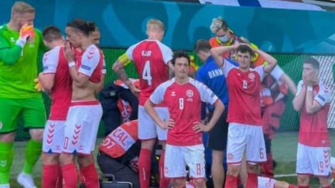 Para pemain Timnas Denmark membuat pagar betis saat tim medis merawat Christian Eriksen yang tiba-tiba pingsan, pada laga perdana Piala Eropa 2020, melawan Finlandia, Minggu (13/6/2021). (Foto : yahooberita)