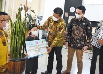Bupati Bandung Dadang Supriatna didampingi Wakil Bupati Sahrul Gunawan menyerahkan hadiah juara baca puis kepada Nizam Adriansyah dari SD Panundaan, di Rumah Jabatannya, Soreang, Kamis (9/9/2021). (Foto: Humas Pemkab Bandung)