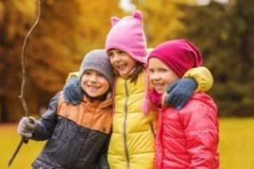 group of happy kids hugging in autumn park for a Happy Thanksgiving