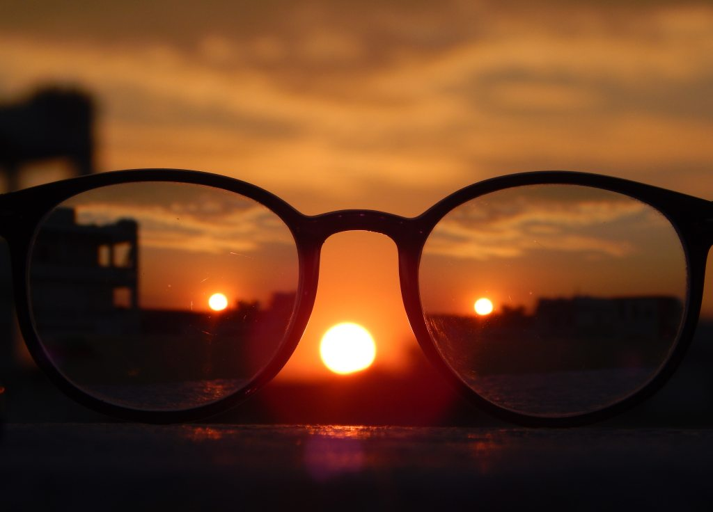 A photo of a pair of reading glasses at sunset, with images of the sunset appear in each lens, and beyond the glasses.