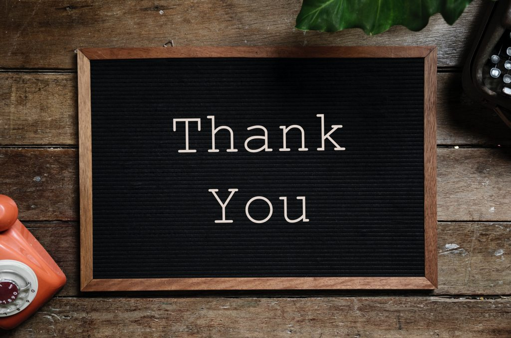 "A black noticeboard with the words ""Thank You"" written in white"