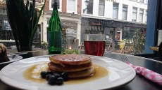 Blueberry pancakes with tea and a rainy backdrop