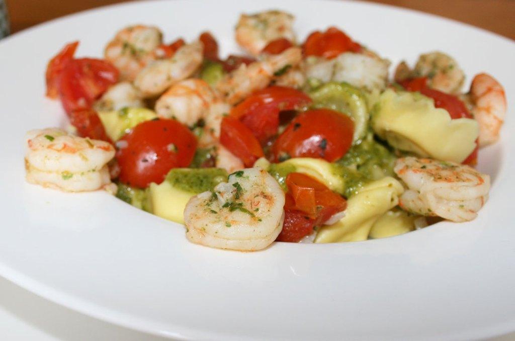 Nahaufnahme von Tortellini Pesto Basilikum mit Scampi und Tomaten. Rezeptbild