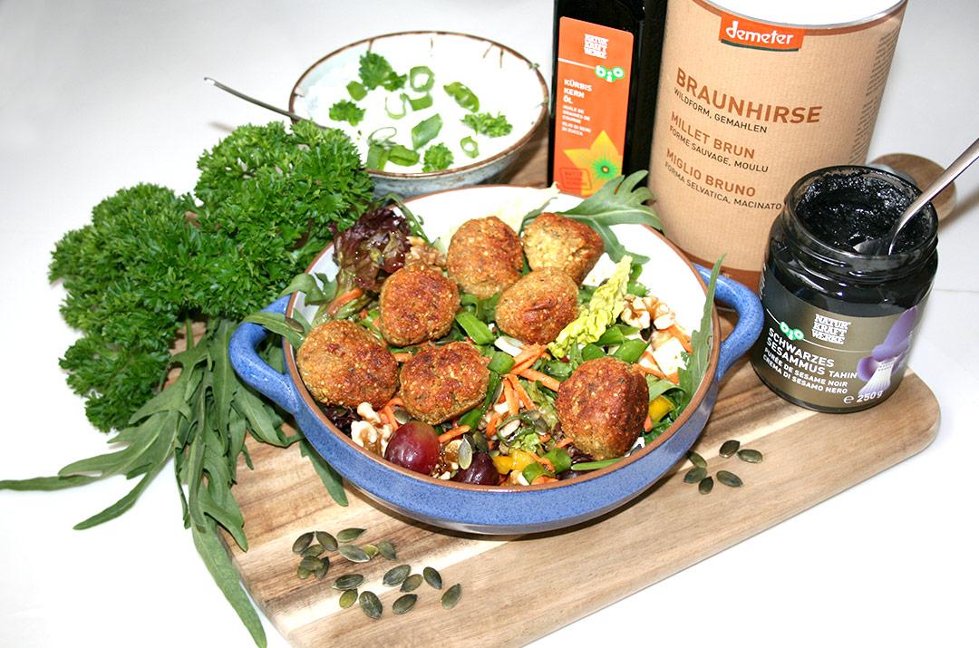 Foto von: Falafel mit Hirse auf buntem Rucolasalat mit Kürbiskernöl und dazu Kräuterquark und schwarzes Sesammus. Darjas Welt