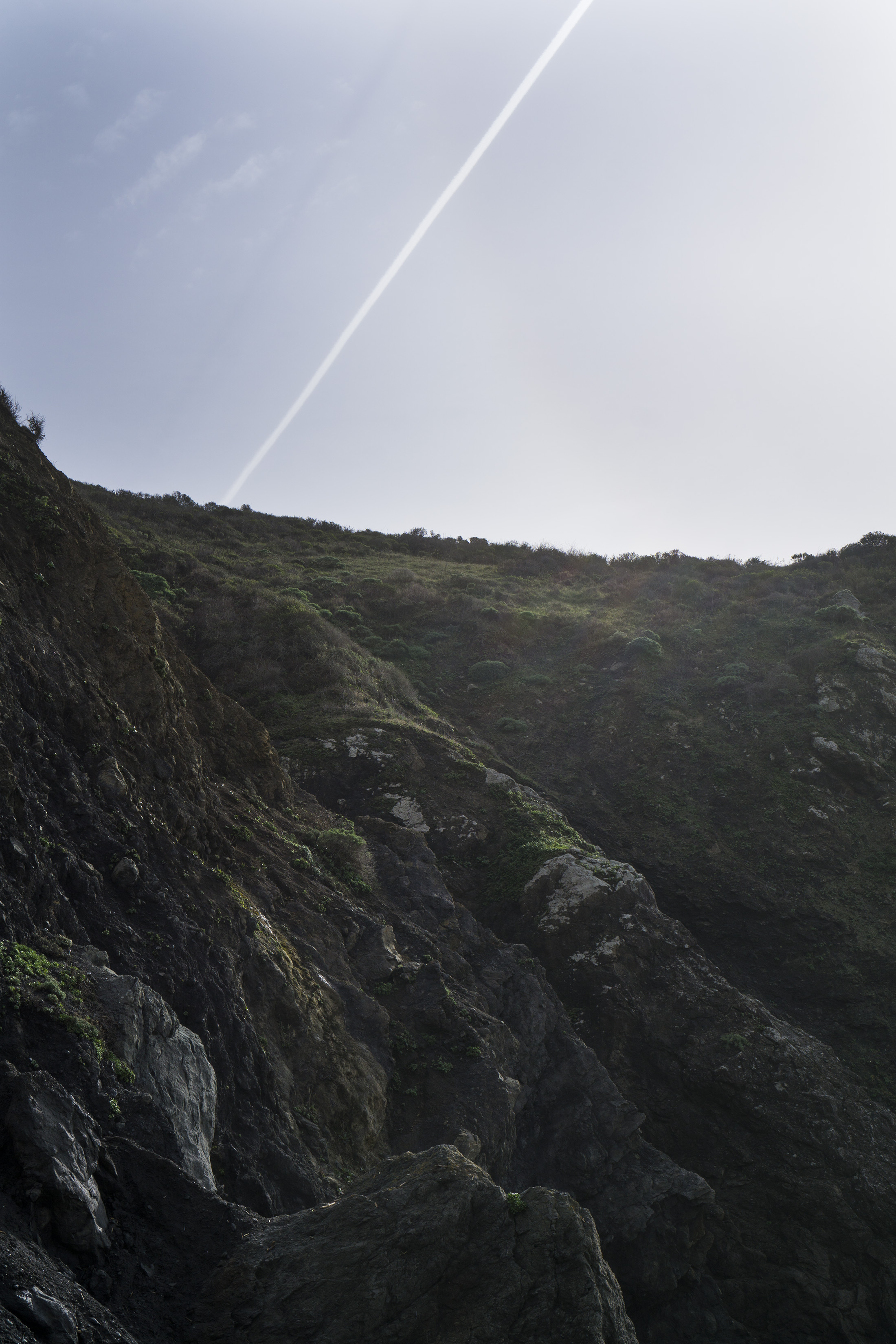 Contrail in the sky behind the cliff at Pirates Cove, Marin Headlands, Golden Gate National Recreation Area / Darker than Green