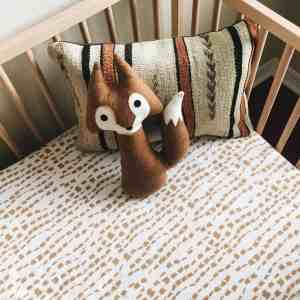 wood crib with stripe pillow and plush brown fox