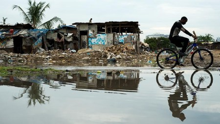 A man cycles down flooded Morogoro Rd on January 20. Photo: Daniel Hayduk
