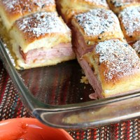 Easy, cheesy Monte Cristo Sliders. If you're obsessed with Hawaiian roll sliders like we are, these will be a great new addition to your list. Honey ham and Swiss cheese pack these sliders, then they're baked with a delish egg topping. Afterwards, you sprinkle with powdered sugar and dunk in jam. YUM! via @DashOfEvans #FridayNightDinner #GilmoreGirls