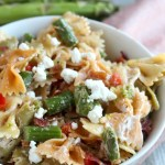 Looking for a fresh new asparagus recipe? Look no further! Using creamy goat cheese and bow tie pasta, this will be a huge hit at your next BBQ! Don't skimp on the crispy bacon! via @DashOfEvans #MIAsparagus