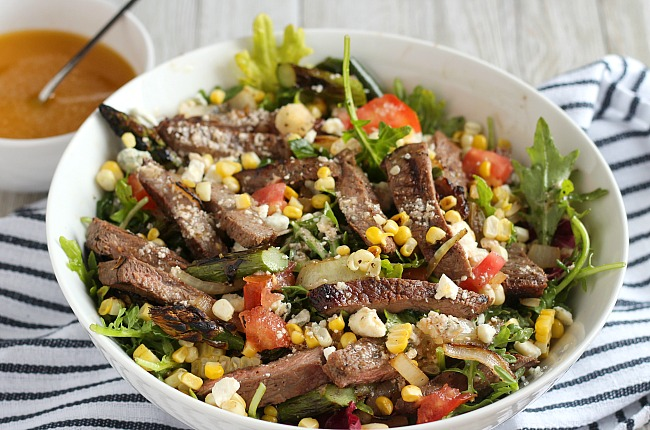 Looking for a new, easy summer salad? The steak is marinaded with whiskey and dijon, then grilled with corn, onion, asparagus and poblano peppers. Perfect balance of flavors for this easy salad! via @DashOfEvans for #Meijer