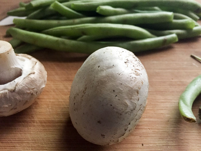 white cello mushrooms and fresh green beans on wooden cutting board