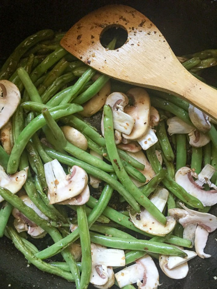 green beans and mushrooms cooking in pan