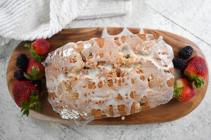 glazed lemon berry quick bread loaf with strawberries and blackberries