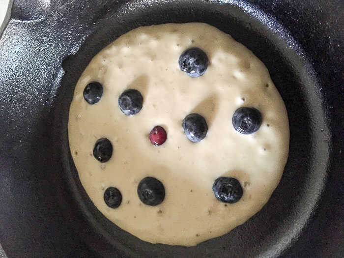cooking blueberry pancake in cast iron skillet