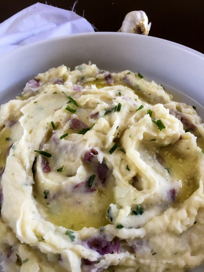 garlic mashed red potatoes garnished with chopped chive and pools of melted butter.