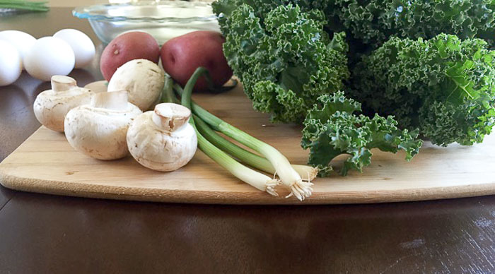 fresh mushrooms, green onions, kale, red potatoes, and eggs on cutting board