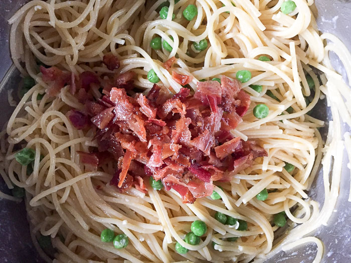 crumbled bacon in pot of spaghetti