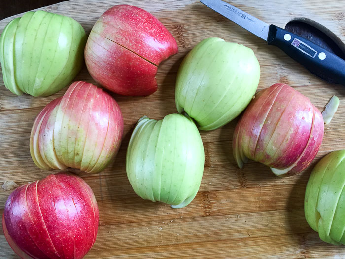 sliced green and red apples on cutting board